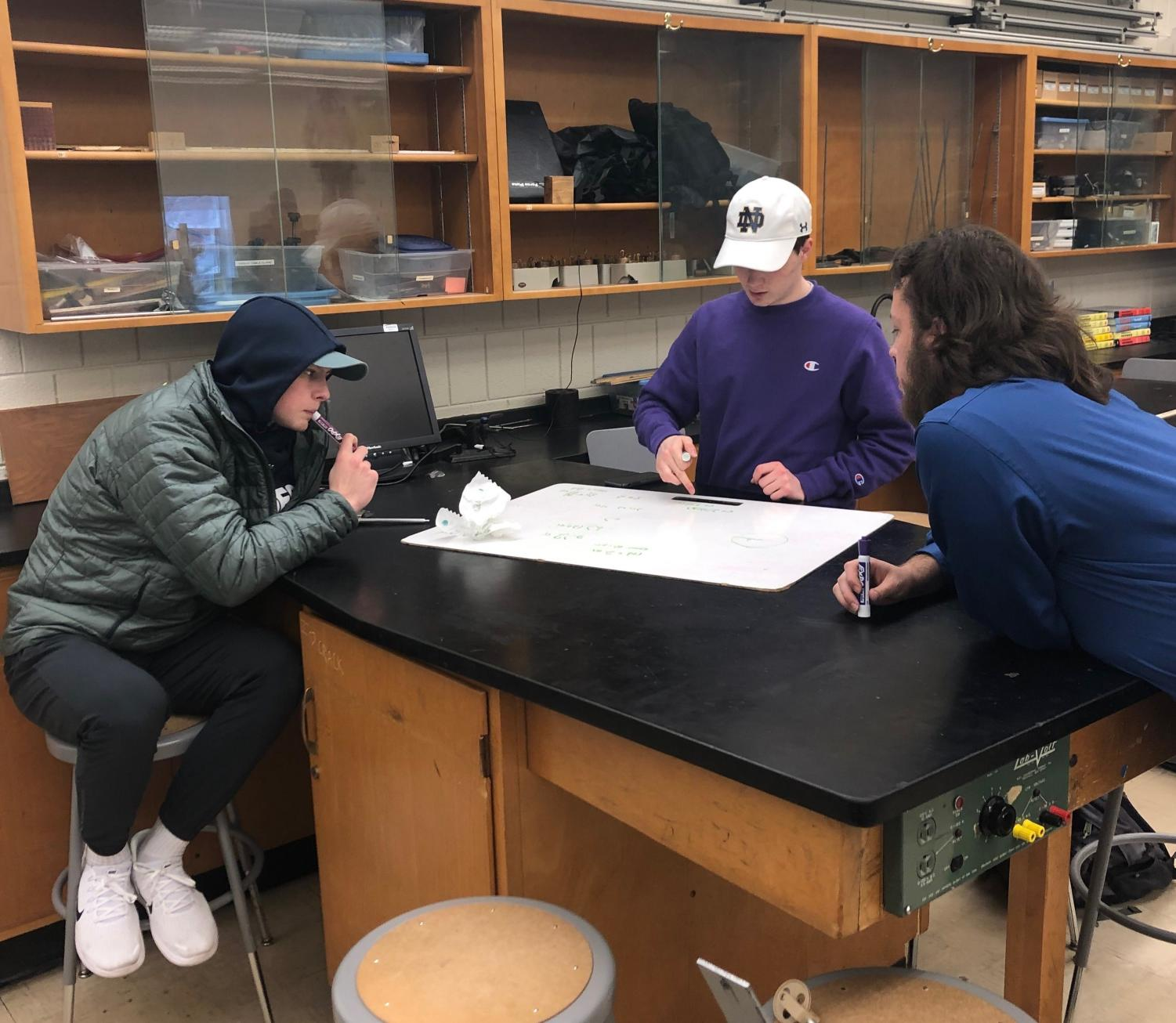 Physics teacher Aaron Pacheco guides Jack Lindstrom and Sean Supan through one of many inquiry-based projects.