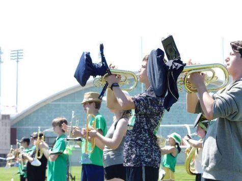 Though the marchers maintain a six-foot distance, woodwinds and brass use bell covers to reduce the spread of germs.